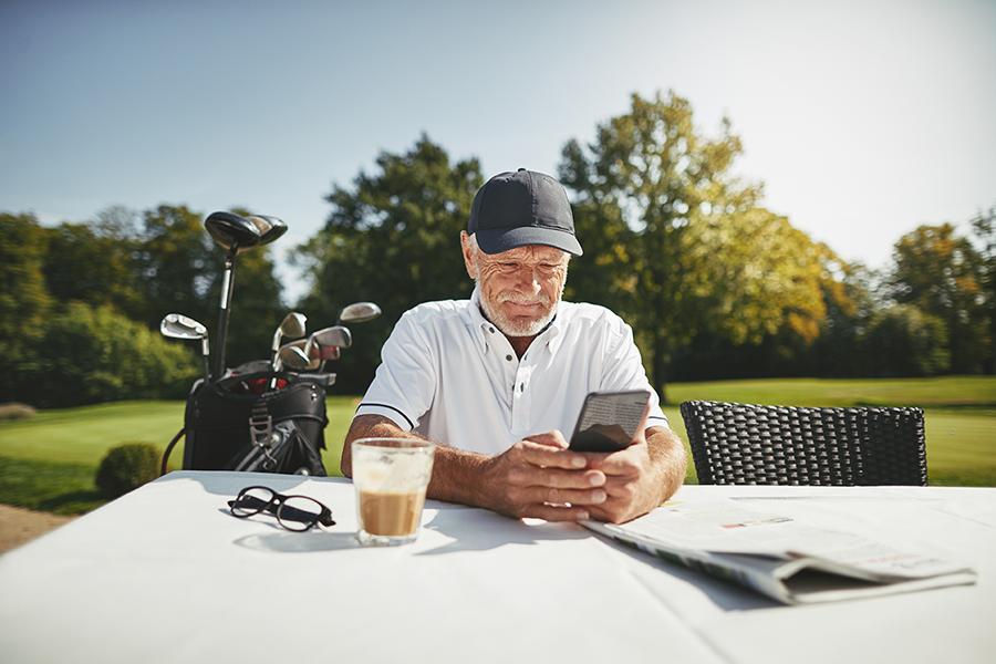 Senior man using a cellphone at his golf club